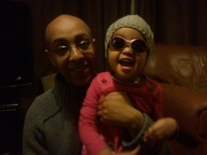 A picture of Fuad holding his daughter Shakila, both are smiling for the camera.