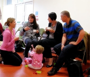 Four adults talking while a toddler sits on the floor playing in front of them