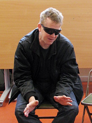 Man indoors sitting with sunglasses on