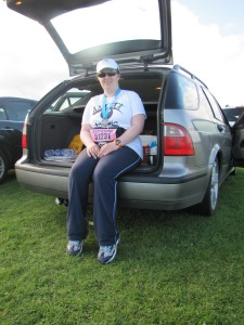 Katie sitting in the open boot of a car, wearing an Aniridia Network UK cap and tshirt