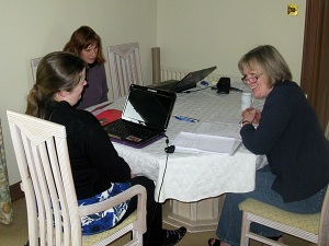 Three women sitting around a table with laptops and meeting papers