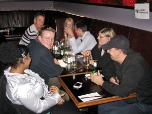 7 people sitting a table in a bar