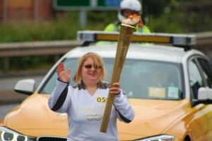 Claire waving and carrying the Olympic Torch followed by a car and police motorcyclist
