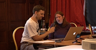 Man and woman speaking into a microphone, seated in front of a laptop and a projector