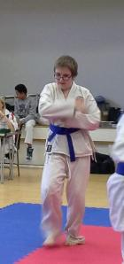 Elliott wearing a white gi with a purple belt