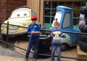 Two boys in front of characters from the film Cars