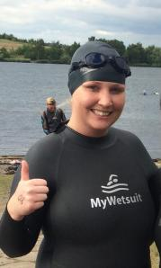Kirsty in a black wet suit and swimming hat at a lake, giving a thumbs up sign