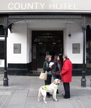 Three woman and a guide dog outside the entrance to The County Hotel