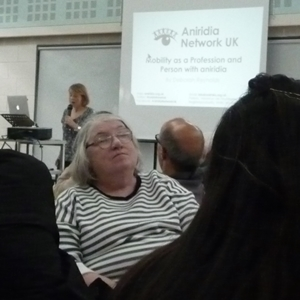 Woman listening with a presenter and screen in the background