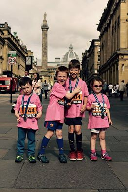 THree boys and a girl of mixed ages under 8 wearing medals over pink tshirts and shorts on a Newcastle street
