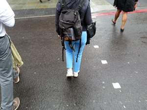 The legs three people crossing a road, the middle one is a woman woman wearing bright blue trousers