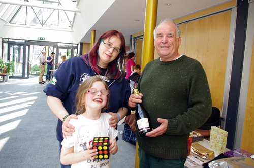 Mum and daughter with a cube toy alongside a man with a bottle of wine