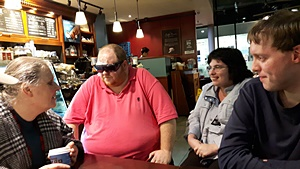 Two women and two men talking while sat around a table in a coffee shop