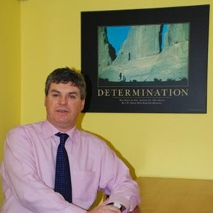 Fintan standing beside a poster on which the main word is determination