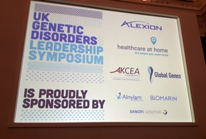 Big screen showing: UK Genetic Disorders Leadship Symposium, Proudly Sponsor by Alexion, Healthcare at Home, Akcea, Global Genes, Alnylam, Biomarin, Sanofi Genzyme