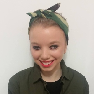 16 year old woman with a two-tone green ribbon in her hair