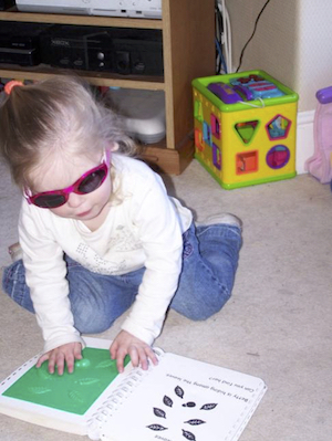 Small girl wearing dark glasses feeling a tactile book while knelling on the carpet