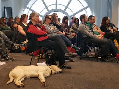 Seated audience and a guide dog laying on the floor