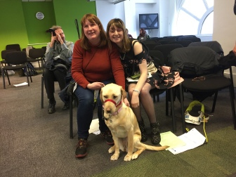 Fern and her guide dog sitting with one of our delegates