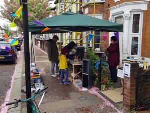A stall under a gazebo in front of a Victorian terraced house