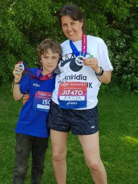 Katja in her Aniridia Network t-shirt, posing with a young boy, both smiling and holding up their half marathon medals
