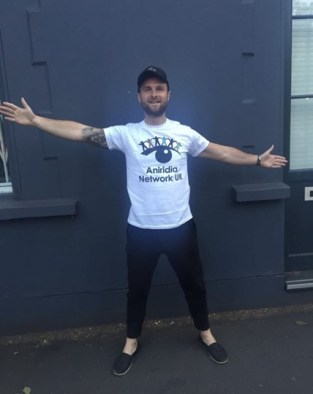 Matt Hill smiling, with arms outstretched, wearing a white Aniridia Network t-shirt, black trousers and a black cap.