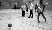 Three people practising bowling a goalball