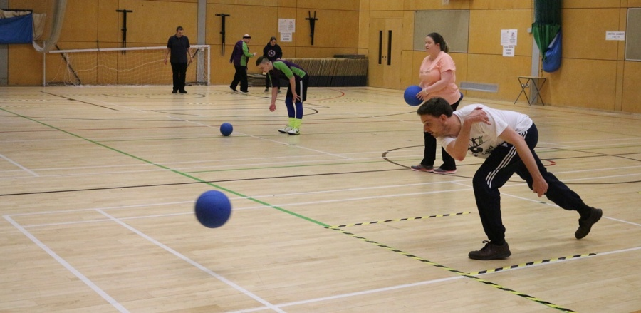 Three people practicing bowling a goalball
