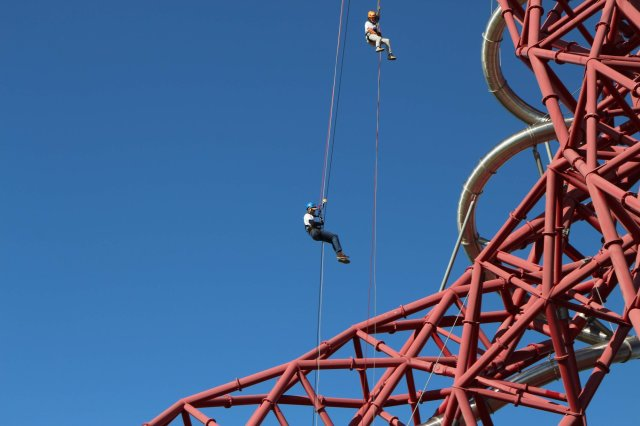 James and another abseiler haning in mid air alongside the red girders of the Orbit tower