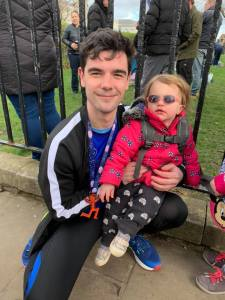 Edward wearing his half marathon medal and holding Sabrina, who has aniridia.