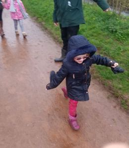 Scarlett looking happy in her dark blue coat and dark glasses as she walks along the muddy path