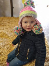 Rhiannon wearing a wooly hat with large colourful bobbles by each ear and on the top.