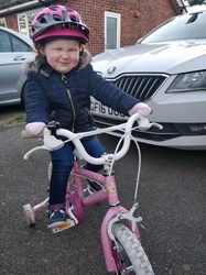 Rhiannon smiling as she rides a pink bike.