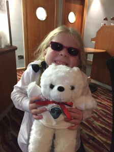 A young girl smiling and wearing sunglasses, while holding a white teddy bear. The bear has a red bow tied around its neck, and is wearing a white t-shirt featuring the Aniridia Day logo.