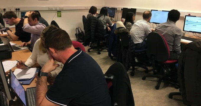 9 people sitting at 7 computers