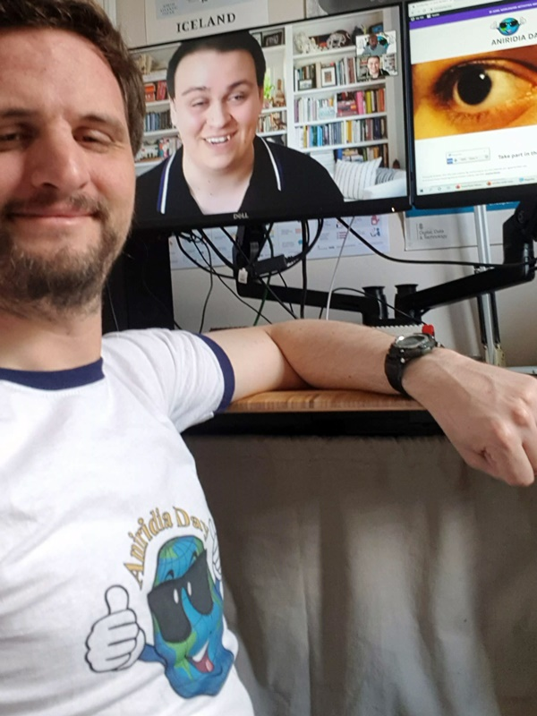James wearing a Aniridia Day t-shirt in front of computer monitors showing Charles Bloc and thete Aniridia Day website