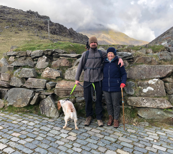 Dog, Nathan, Tricia with a walking sticking with Snowdon in the backgruond